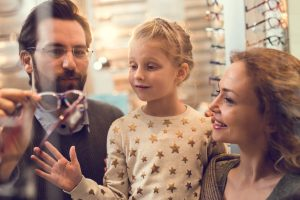 Smiling family choosing the most suitable eyeglasses in a store. Focus is on girl.